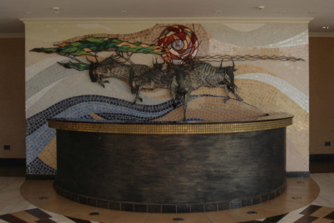 Mara crossing Mosaic: Ceramic tiles Wildbeest, mara river, acacia, thorn tree, sun, savanna. Created in steel, stained glass and tile mosaic. Piece at Brookhouse school in Nairobi, Kenya Style: Stylised Theme: Nature african mosaic art by Kenyan artist